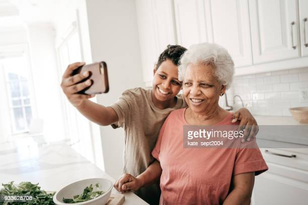 Grandmother and son taking selfie with cellphone in the kitchen