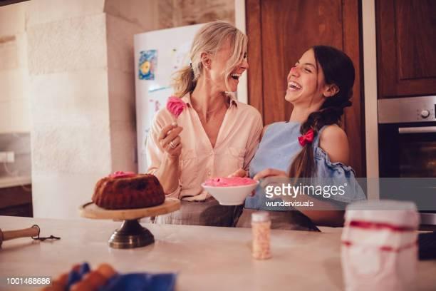 avó e neta adolescente de cozimento e confeiteiro bolo juntos - fazer um bolo - fotografias e filmes do acervo