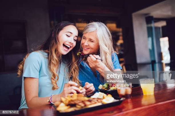 grandmother and teenage granddaughter eating a meal at a restaurant - senior lunch stock photos and pictures