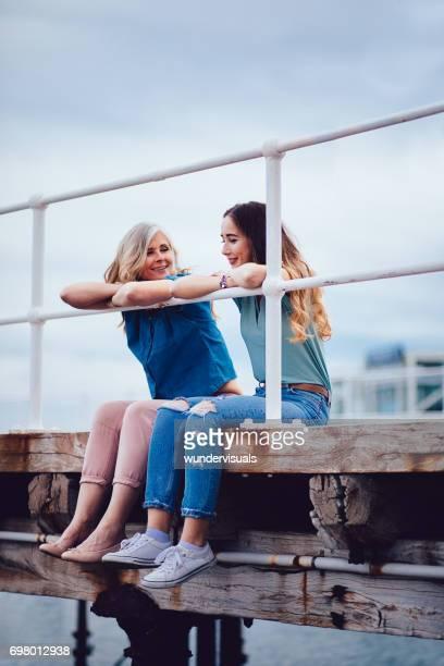 Großmutter und Teenager Enkelin Spaß sitzen auf einem Steg