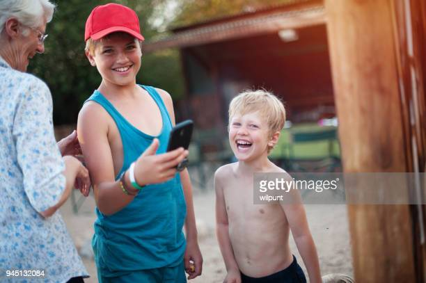 grandmother and two boys laughing together with mobile phone outdoors - the karoo stock pictures, royalty-free photos & images