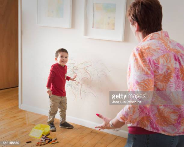 Grandmother angry at grandson drawing on wall with crayons