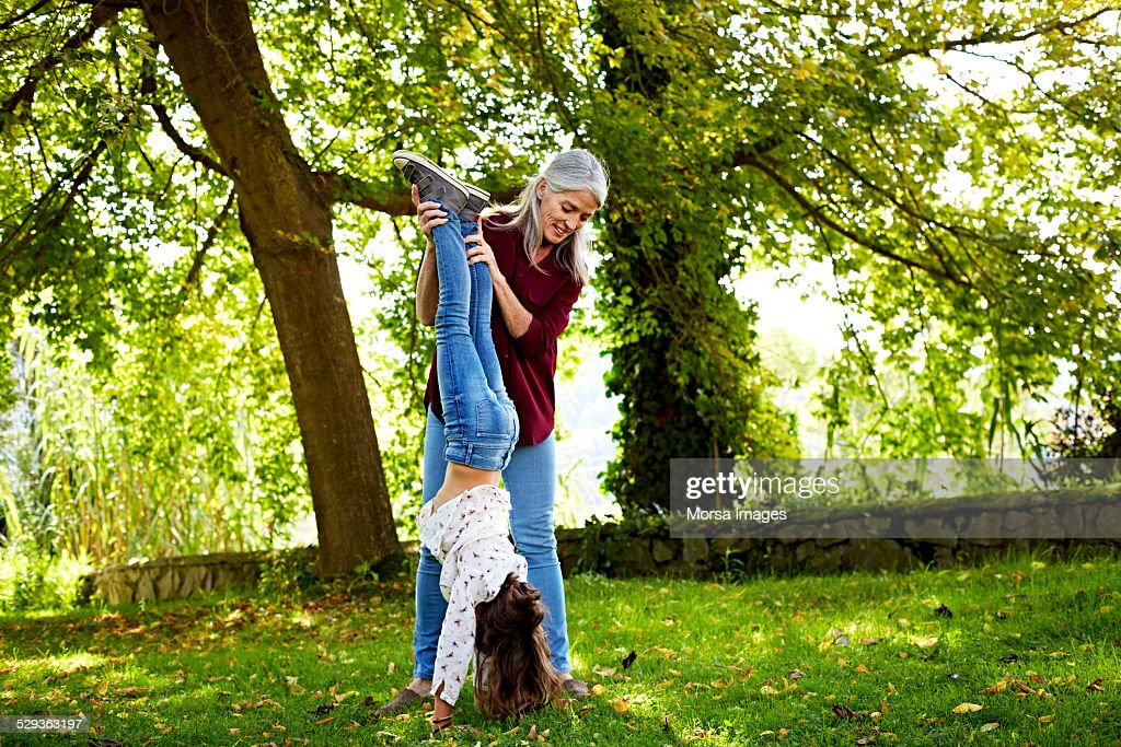 Grandmother assisting girl in doing handstand : Stock Photo
