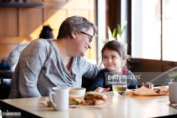 grandmother at coffee shop with her sweet granddaughter - chubby granny fotografías e imágenes de stock