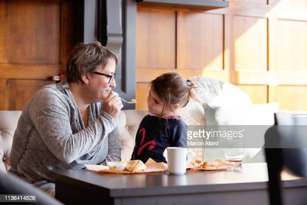 grandmother at coffee shop with her sweet granddaughter - chubby granny stock pictures, royalty-free photos & images