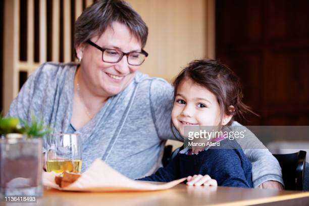 grandmother at coffee shop with her sweet granddaughter - fat granny stock pictures, royalty-free photos & images