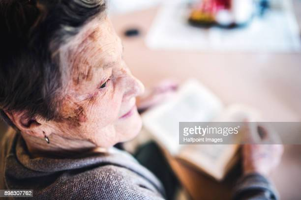 Grandmother at home reading a book.