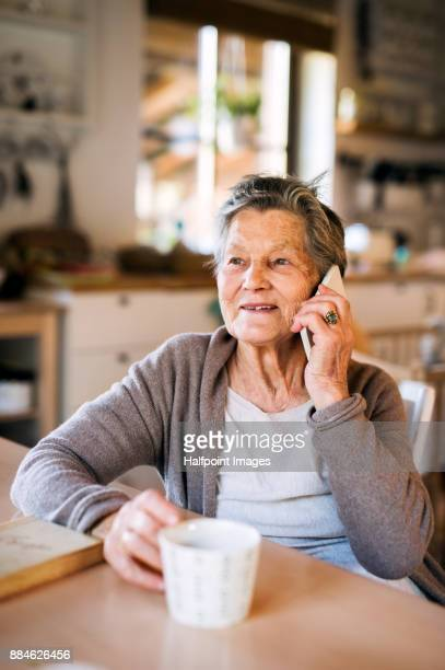Grandmother at home using smart phone.
