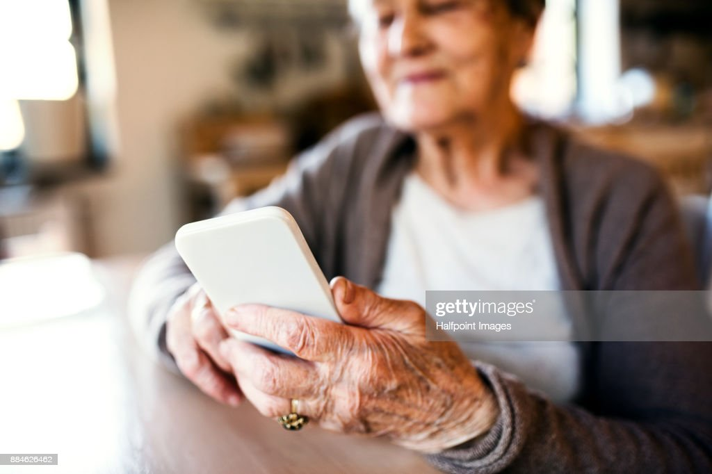 Grandmother at home using smart phone. : Stock Photo