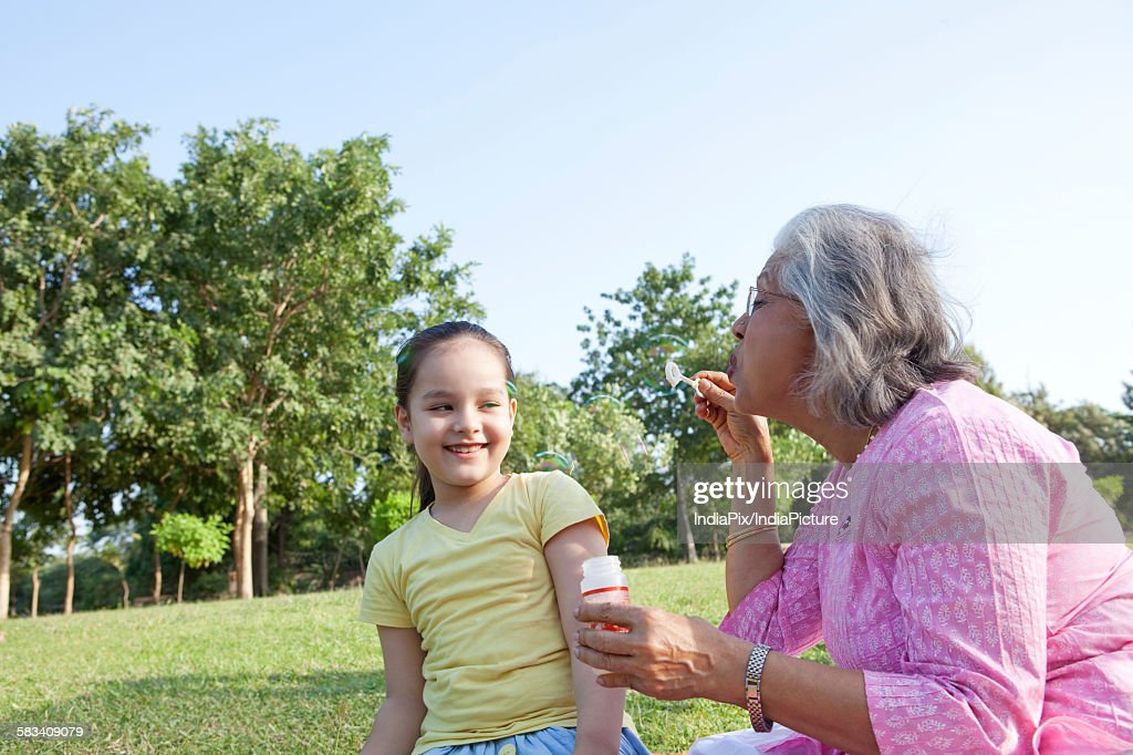Grandmother blowing bubbles at granddaughter : Stock Photo