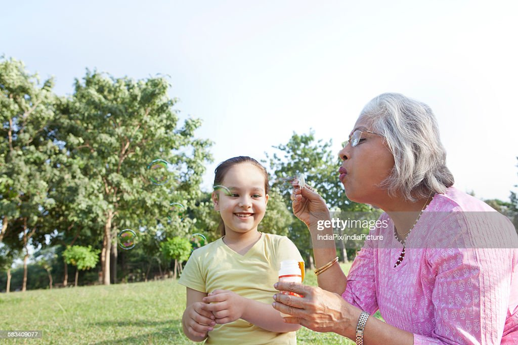 Grandmother blowing bubbles for granddaughter : Stock Photo