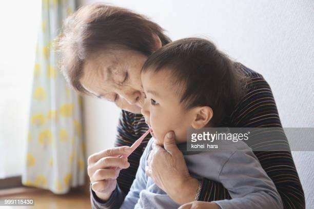 祖母は彼女の孫の歯を磨く