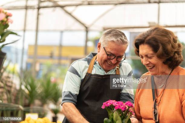 grandmother buying flowers market - 60 69 years stock pictures, royalty-free photos & images