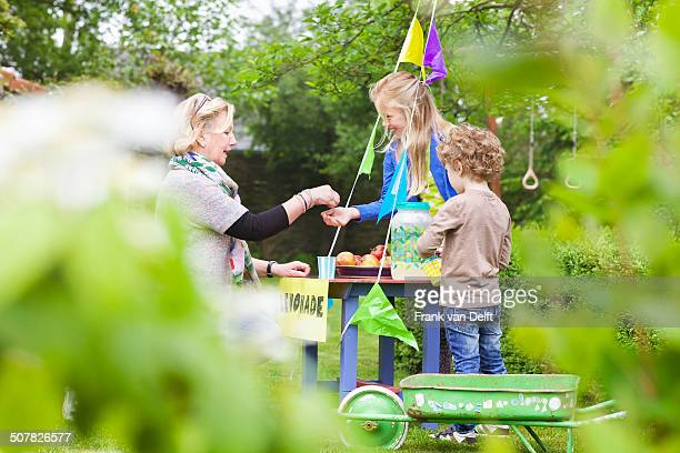 grandmother buying lemonade from grandchildren's stand - fundraising stock pictures, royalty-free photos & images