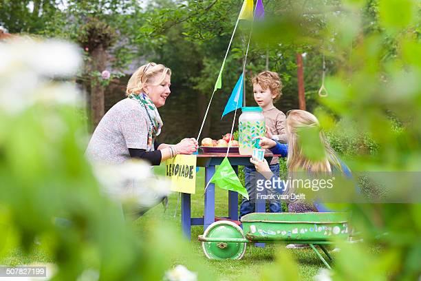 Grandmother buying lemonade from grandchildren's stand