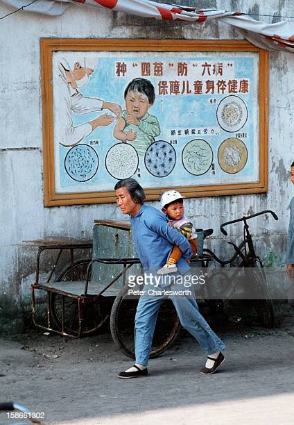 A grandmother carries her grandchild past a healthcare poster on a wall The poster depicts a child being vaccinated by a nurse Many grandparents act...