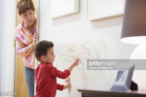 Grandmother catching grandson drawing on wall with crayons