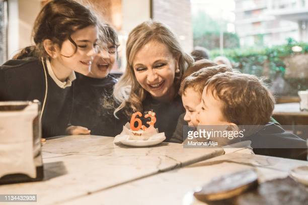 grandmother celebrating her birthday with grandchildren - happybirthdaycrown stock pictures, royalty-free photos & images