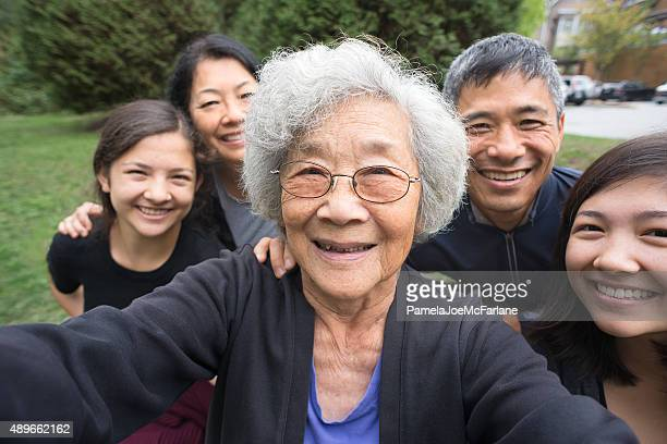 grandmother, children, grandchildren pose for selfie, care home in background - east asian culture stock photos and pictures