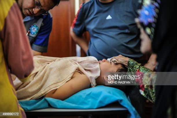 A grandmother comforts his grandson as he undergoes circumcision during a mass circumcision ceremony at a mosque in Ampang in the suburbs of Kuala...