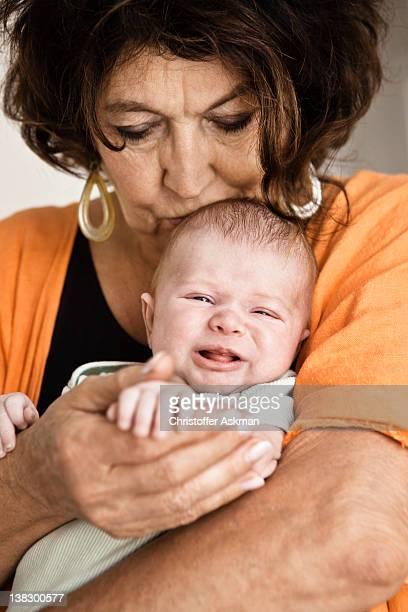 Grandmother cradling crying infant