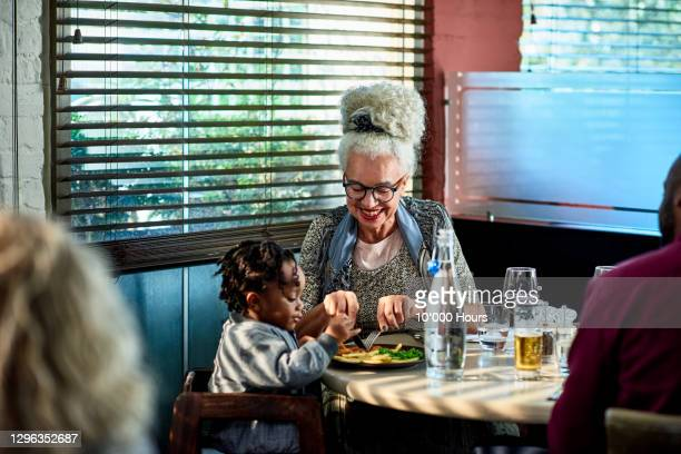 grandmother cutting child's food in restaurant - childhood stock pictures, royalty-free photos & images