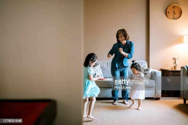 grandmother dances with grandchildren at home - korean ethnicity stock pictures, royalty-free photos & images