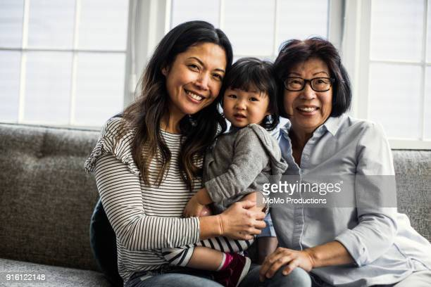 grandmother, daughter and granddaughter on couch at home - multigenerational family stock photos and pictures