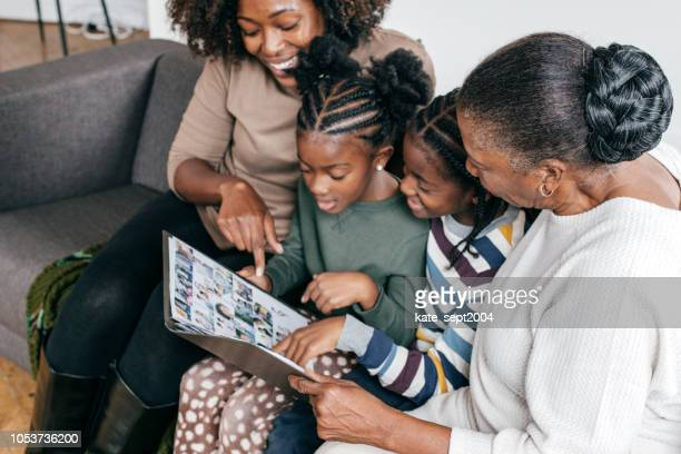 grandmother, daughter and grandkids looking at photo album - photo album stock pictures, royalty-free photos & images
