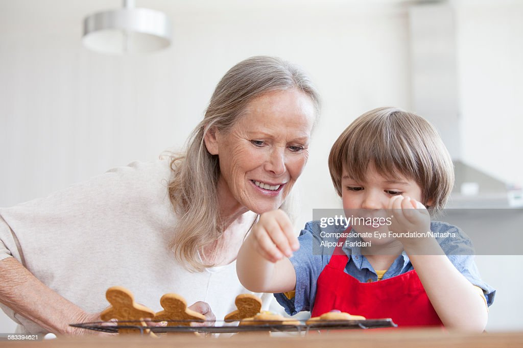 Grandmother decorating cookies with grandson : Stock Photo