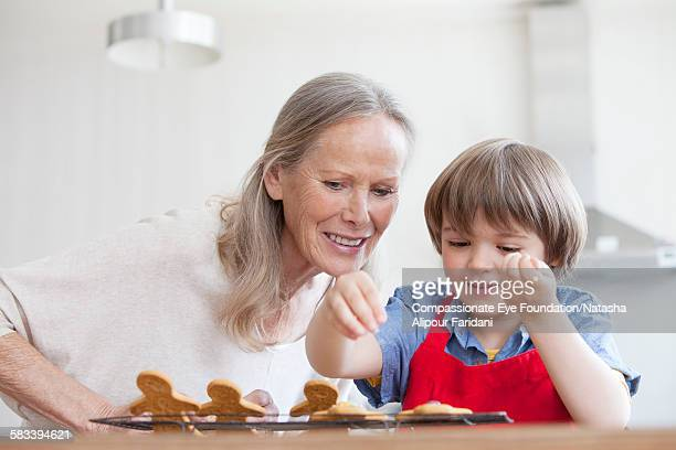 grandmother decorating cookies with grandson - british granny stock photos and pictures