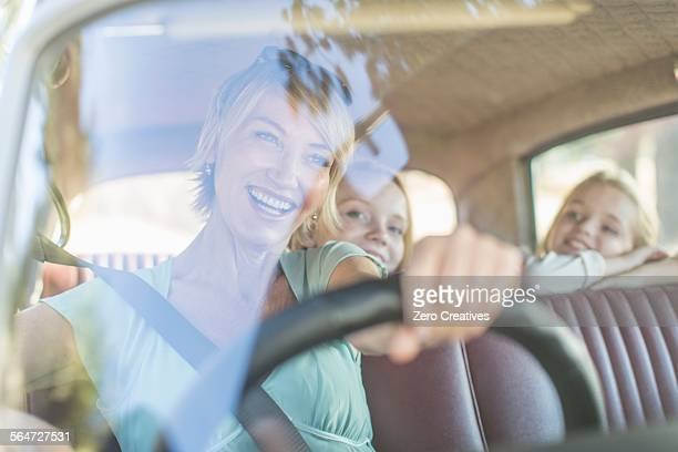 Grandmother driving car, granddaughters sitting in back seat