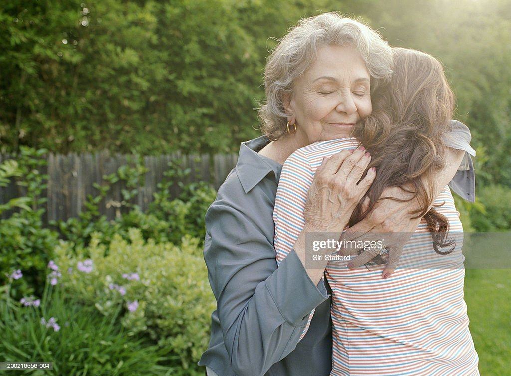 Grandmother embracing adult granddaughter : Stock Photo