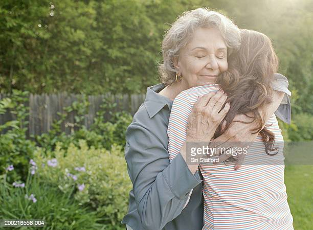 grandmother embracing adult granddaughter - embracing stock pictures, royalty-free photos & images