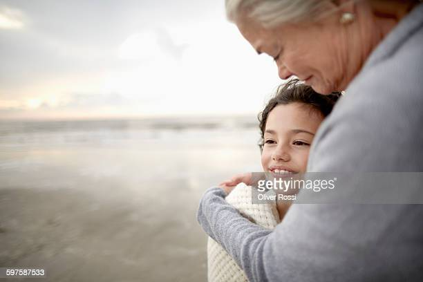 grandmother embracing granddaughter on the beach - 孫娘 ストックフォトと画像