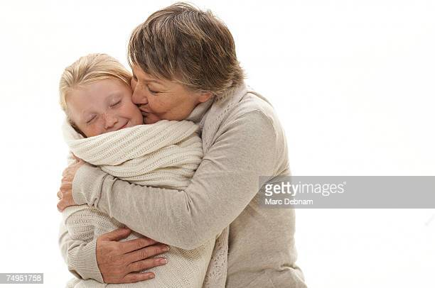 grandmother embracing granddaughter (7-9) - avvolto foto e immagini stock