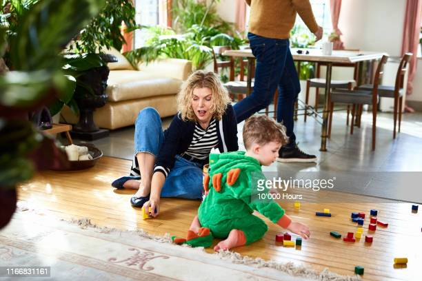 grandmother encouraging little boy to play with wooden blocks - fun stock pictures, royalty-free photos & images