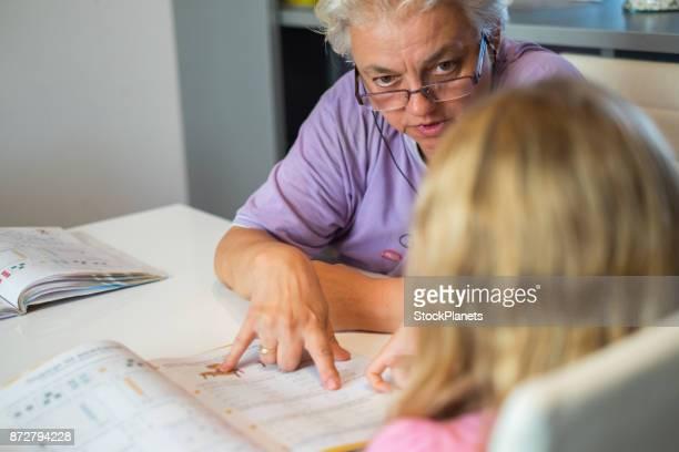 Grandmother explaining homework to her granddaughter