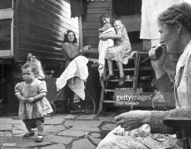 Grandmother Eyres keeps an eye on the children whilst she prepares the supper on a gypsy encampment in Ash, Surrey. Despite their lifestyle, the...