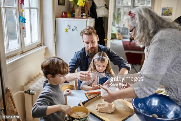 Grandmother, father and children baking at home