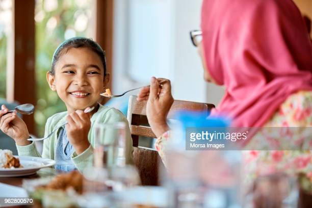 grandmother feeding food to smiling girl at home - malay stock photos and pictures