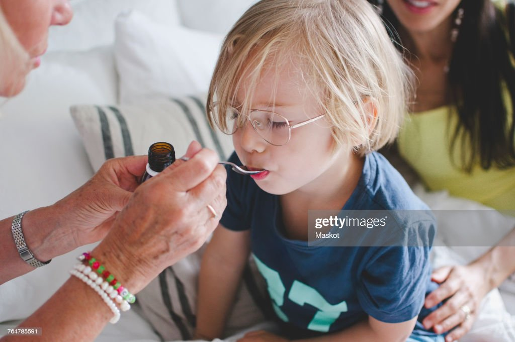 Grandmother feeding medicine to boy with woman sitting in background : Stock Photo