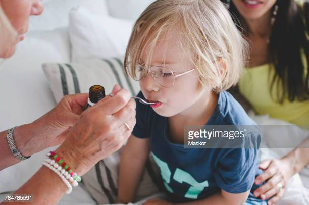 Grandmother feeding medicine to boy with woman sitting in background