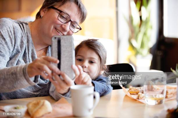 grandmother getting at coffee shop with her sweet granddaughter - chubby granny fotografías e imágenes de stock