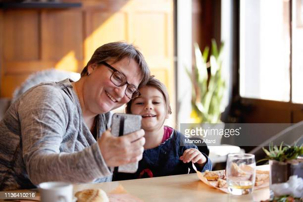 grandmother getting at coffee shop with her sweet granddaughter - chubby granny stock pictures, royalty-free photos & images