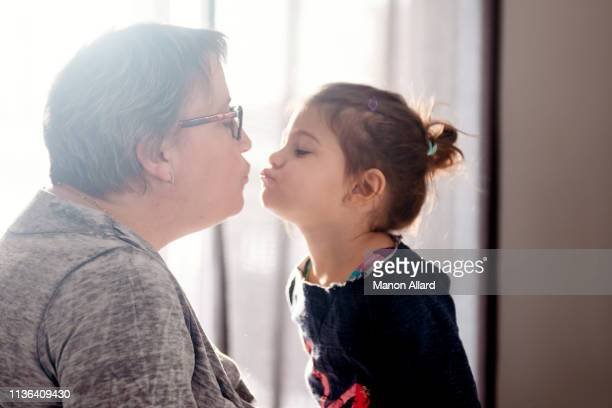 grandmother give a kiss to her sweet granddaughter - fat granny stock pictures, royalty-free photos & images
