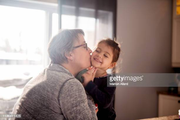 grandmother give a kiss to her sweet granddaughter - grandmother stock pictures, royalty-free photos & images