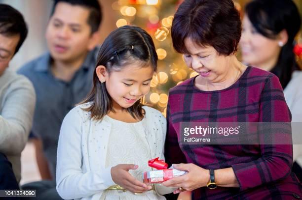 großmutter gibt enkelin ein weihnachtsgeschenk - gift lounge stock-fotos und bilder