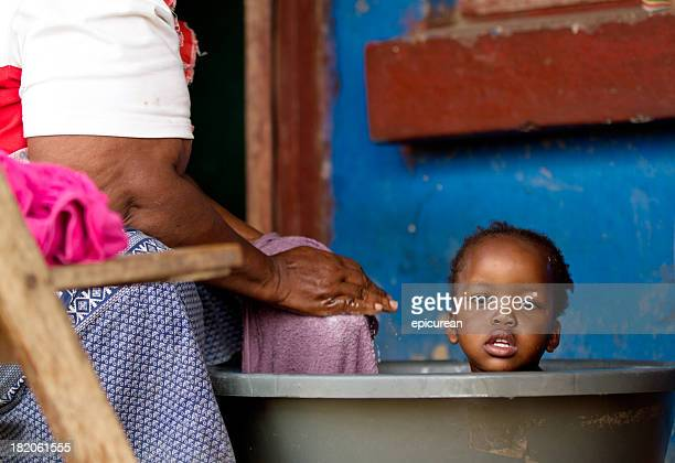 grandmother gives her granddaughter a bath in rural south africa - south african culture stock photos and pictures