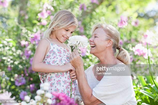 Grandmother giving flower to granddaughter in garden